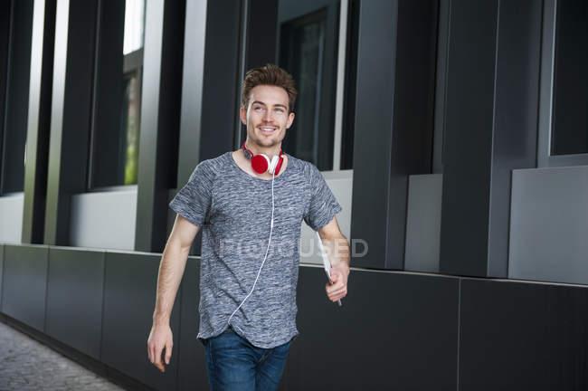 Retrato de jovem caminhando com fones de ouvido e tablet digital — Fotografia de Stock
