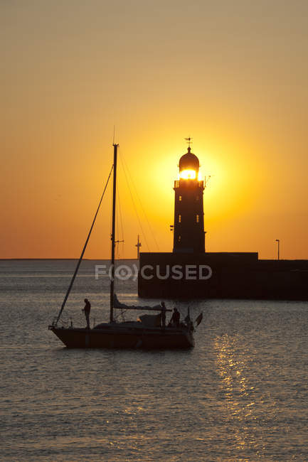 Lighthouse on the pier at sunset — Stock Photo