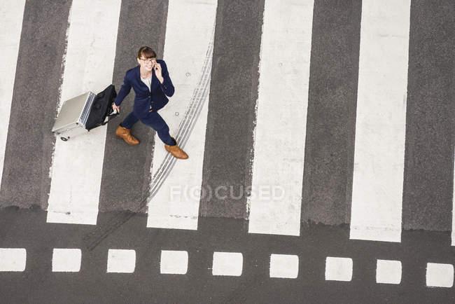 Donna di affari con la valigia che cammina sulle strisce pedonali con smartphone di rotolamento — Foto stock