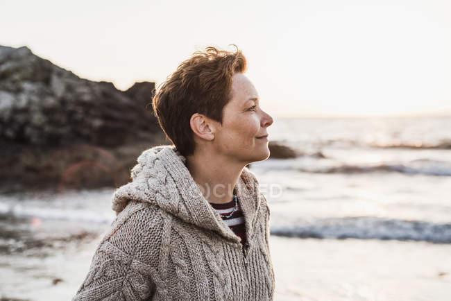 Sonriente mujer de pie en la playa al atardecer - foto de stock