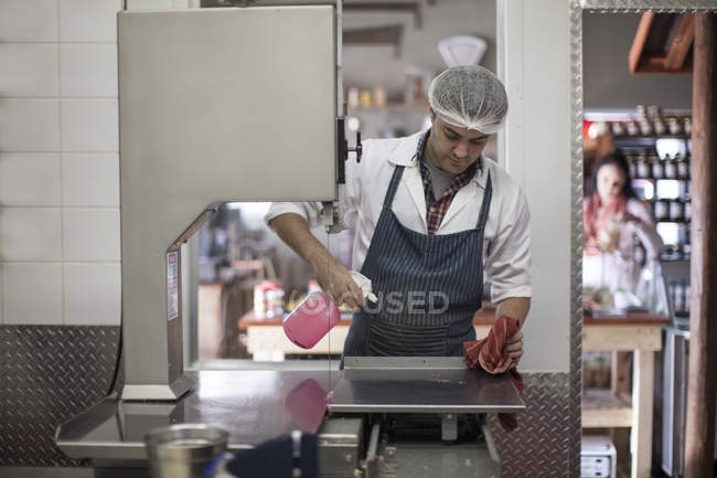 Butcher cleaning work surface in butchery — Stock Photo
