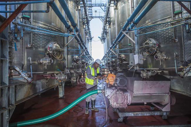 Travailleur dans la cave de contrôle des réservoirs de vin — Photo de stock
