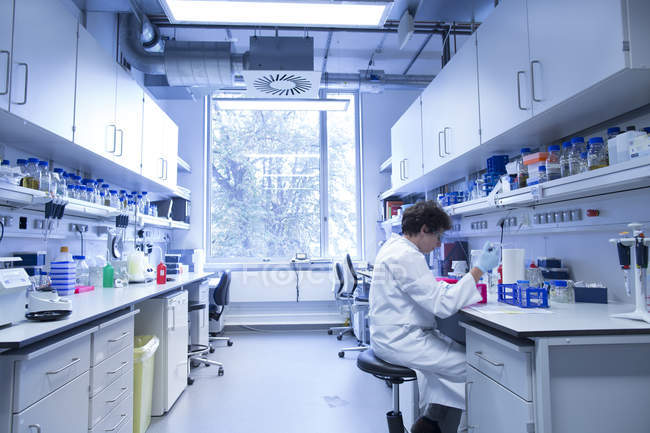 Biologiste féminine travaillant dans un laboratoire — Photo de stock
