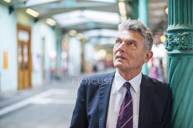 Senior-Geschäftsmann an der Säule schaut auf — Stockfoto