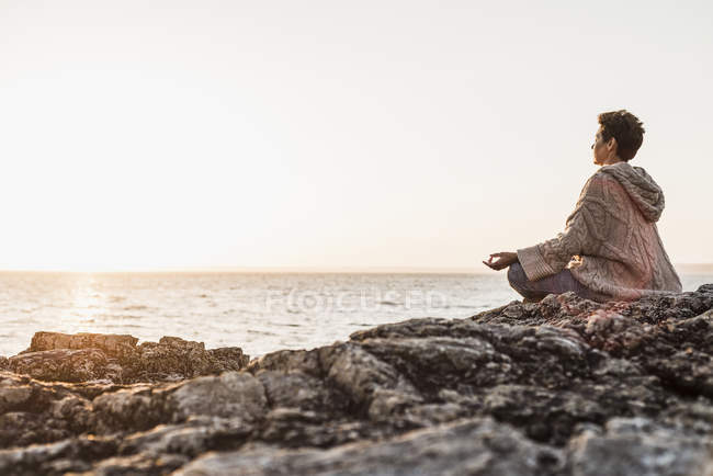 Mulher sentada na rocha na praia e desfrutar do pôr do sol — Fotografia de Stock