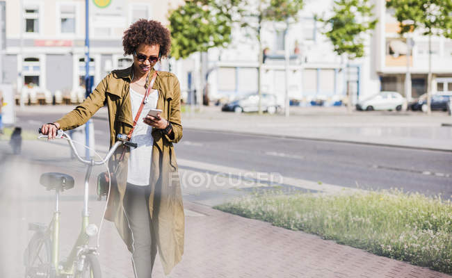 Young woman looking at her smartphone while pushing bicycle — Stock Photo