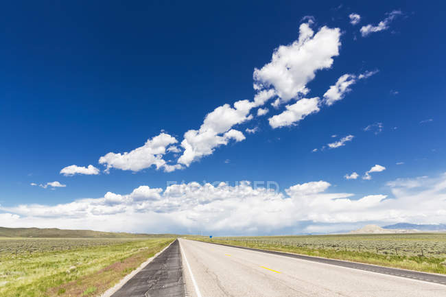 USA, Wyoming, Empty highway 26 and clouds in blue sky — Stock Photo