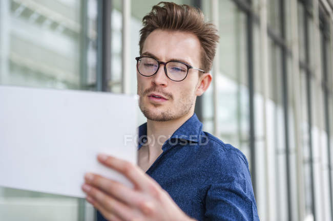 Portrait of young businessman with  digital tablet in front of an office building — Stock Photo