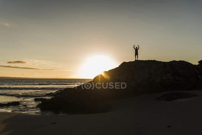 France, péninsule de crozon, jeune homme sur le rocher au coucher du soleil — Photo de stock