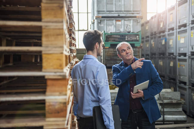 Manager talking to colleague between pallets — Stock Photo