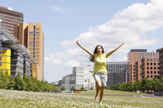 Германия, Берлин, счастливая молодая женщина, танцующая на лугу возле Потсдамской площади — стоковое фото