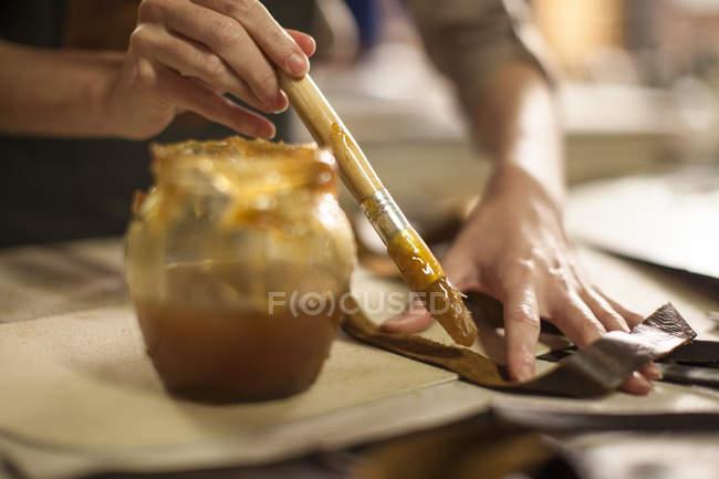 Крупным планом женщина склеивания кожи листов в кожевенной мастерской — стоковое фото