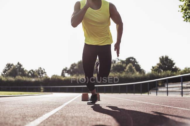 Обітнутого зображення бігун на тартановим трек починаючи — стокове фото