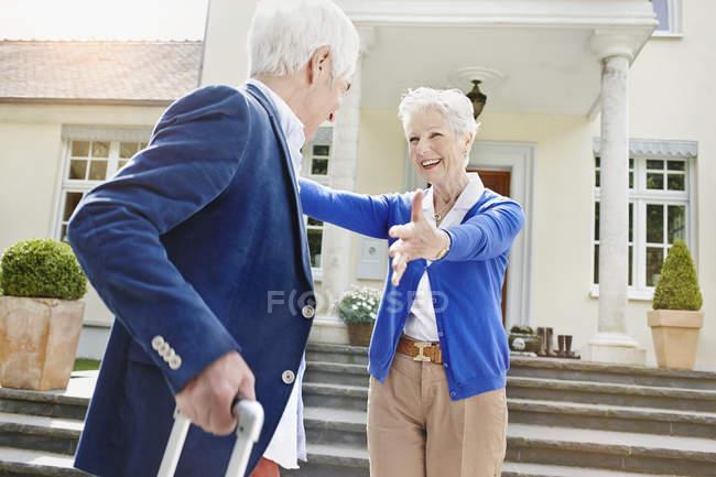 Pareja mayor frente a la villa, mujer acogedora hombre - foto de stock