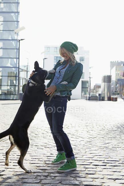 Giovane donna che gioca con il suo cane — Foto stock