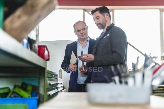 Ingenieure mit digitalem Tablet in der Werkstatt, Mann mit Werkzeug — Stockfoto