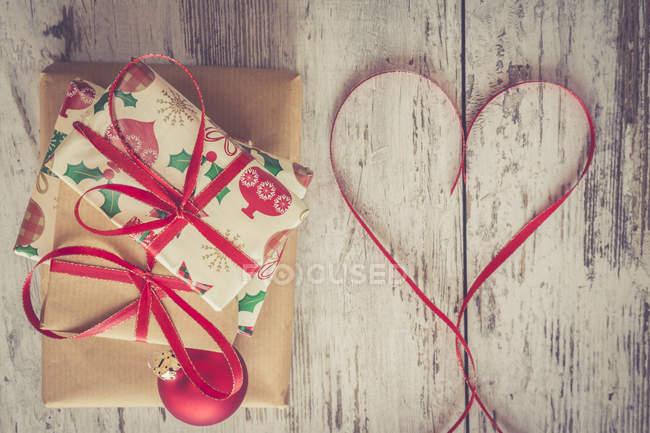 Pilha de presentes de Natal, bugiganga de Natal vermelho e fita em forma de coração em madeira — Fotografia de Stock