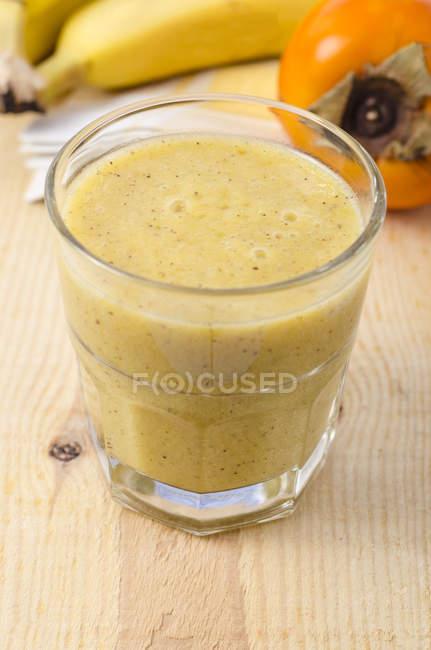 Glass of Kaki smoothie on wood — Stock Photo