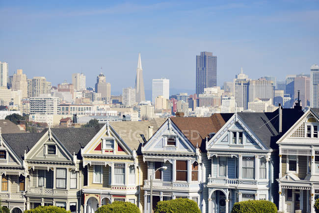 USA, California, San Francisco, Victorian houses at Alamo Square in front of the skyline — Stock Photo