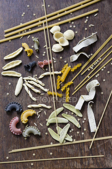 Different sorts of pasta on brown wood — Stock Photo