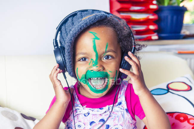 Portrait of happy little girl with painted face listening music with headphones — Stock Photo