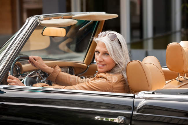 Portrait of mature woman sitting in a convertible car — Stock Photo