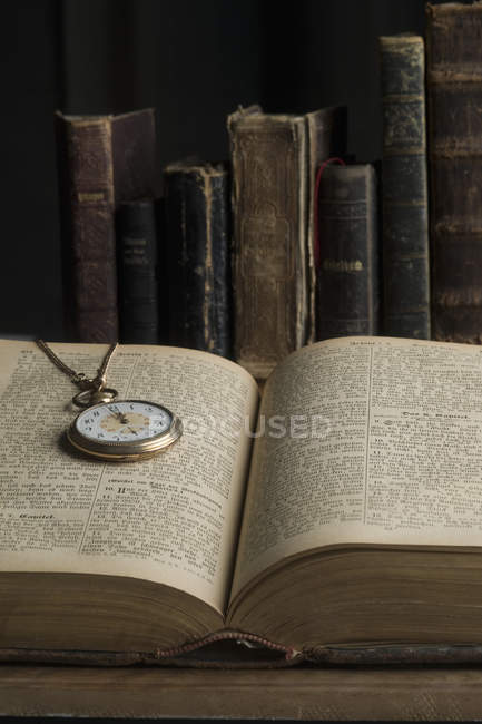 A ouvert le livre avec la vieille montre de poche — Photo de stock