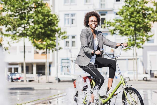 Портрет улыбающейся женщины на велосипеде — стоковое фото