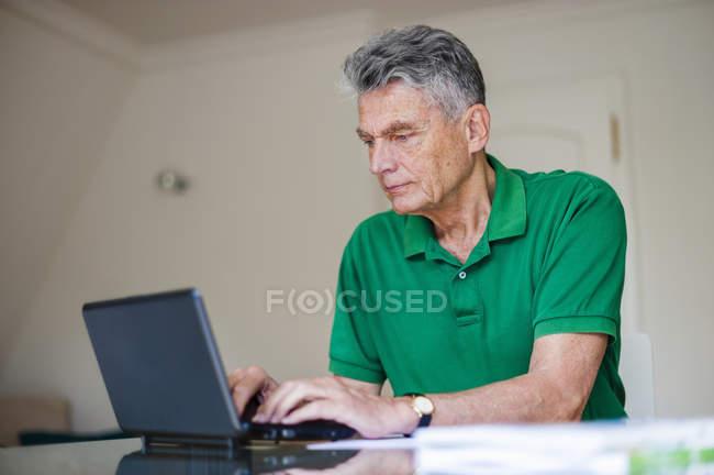 Senior sitzt mit Laptop am Schreibtisch — Stockfoto