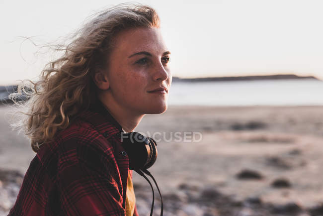 Teenagermädchen mit Kopfhörern schaut Strand weg — Stockfoto