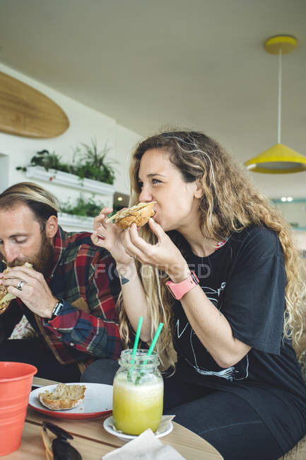 Пара, завтрака в кафе, едят бутерброды и органические соки — стоковое фото