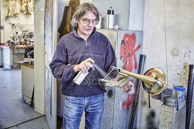 Instrument maker using spray can for trumpet — Stock Photo