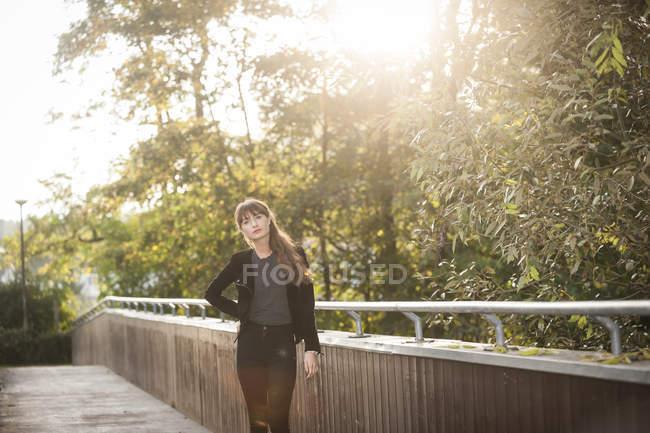 Серьёзно выглядящая молодая женщина, стоящая на пешеходном мосту на заднем плане — стоковое фото