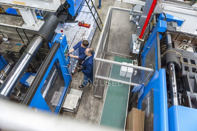Manager and worker having work meeting in plastics factory — Stock Photo