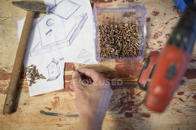 Top view of tools and plan laid out of birdhouse in workshop — Stock Photo