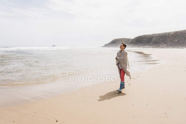Mature woman wrapped in blanket walking on the beach — Stock Photo