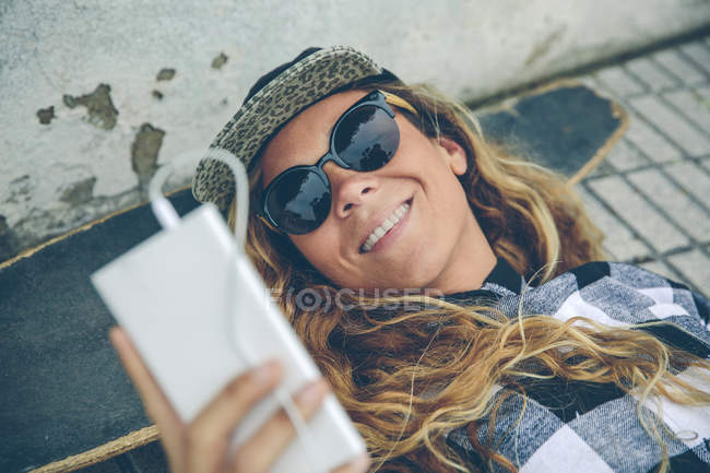 Smiling young woman lying on skateboard looking at cell phone — Stock Photo