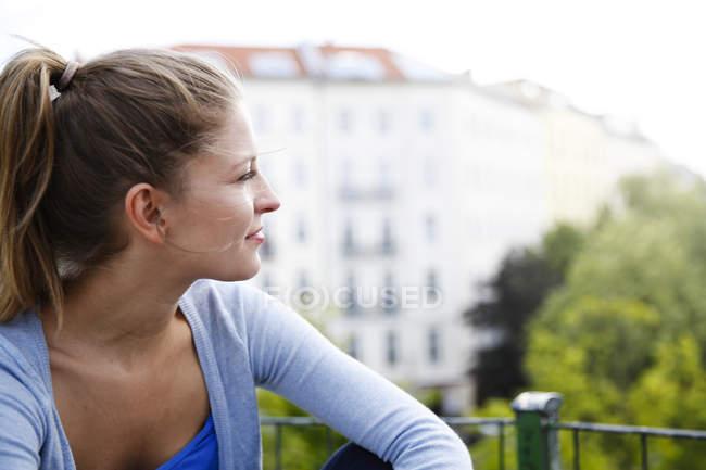 Усміхаючись молода жінка дивиться вбік, на відкритому повітрі — стокове фото