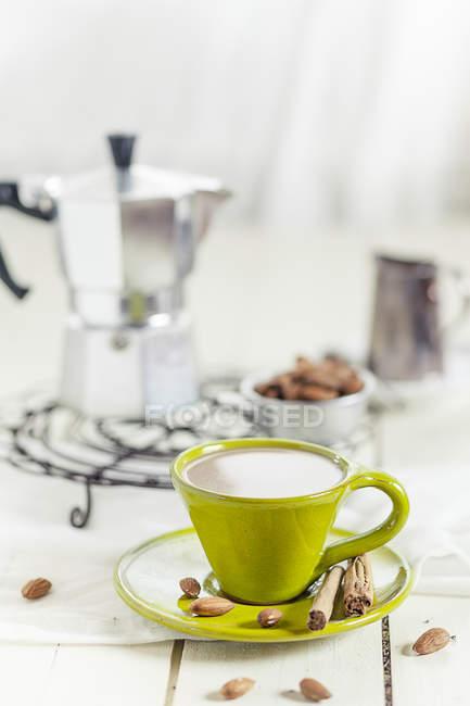 Чашка кофе с миндальным молоком, миндалем и коричными палочками — стоковое фото
