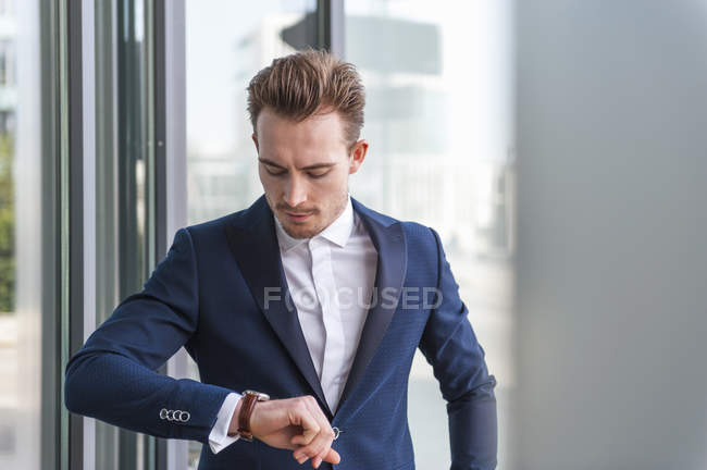Portrait of young man wearing suit checking the time — Stock Photo