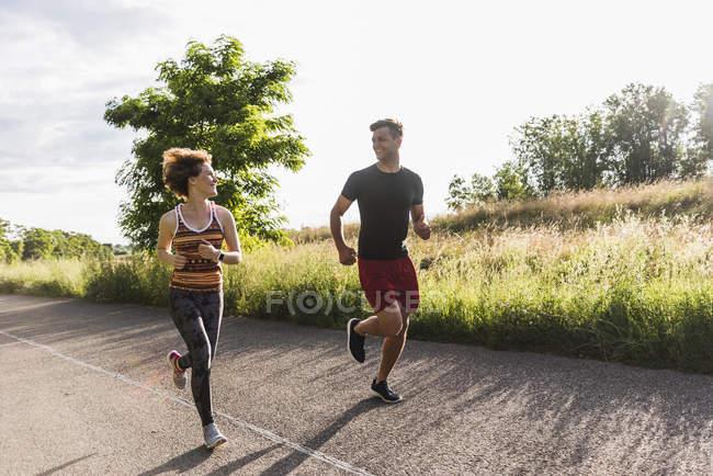Jovem casal correndo na estrada no campo — Fotografia de Stock