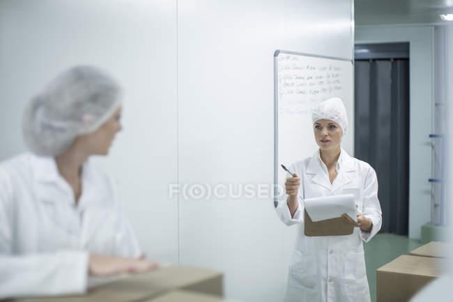 Mulher com prancheta instruindo de trabalho na fábrica — Fotografia de Stock