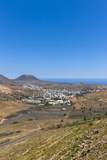 España, Islas Canarias, Lanzarote, Maguez, Pueblo Haria y Volcán Monte Corona en el fondo - foto de stock