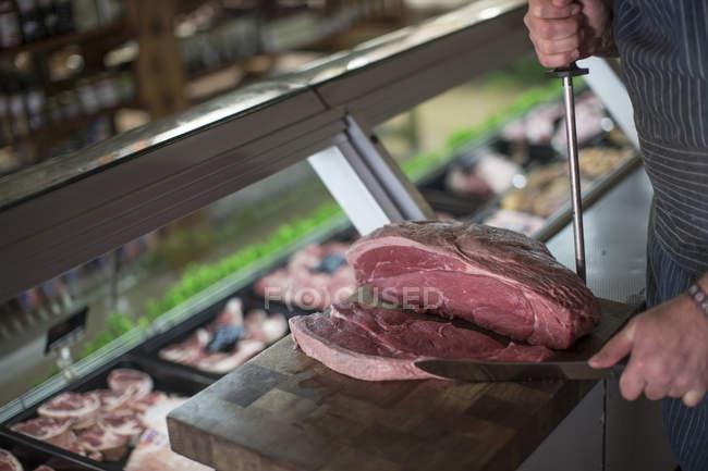 Butcher cutting raw steak on wooden board — Stock Photo