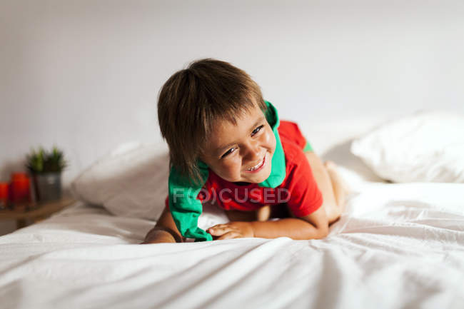 Laughing little boy playing on bes — Stock Photo