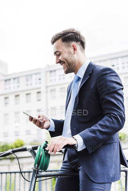 Uomo d'affari con bicicletta a piedi in città, utilizzando smartphone — Foto stock