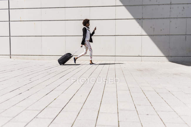 Walking businesswoman with trolley bag looking at her smartphone — Stock Photo