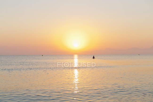 Espagne, Îles Baléares, Majorque, Cala de Muro, homme en mer au coucher du soleil — Photo de stock