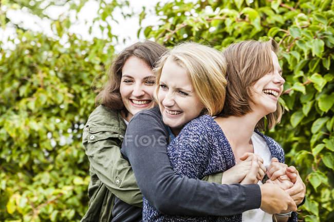 Três amigas abraçando no jardim — Fotografia de Stock