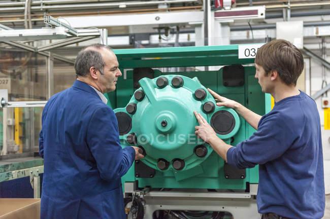 Two men examining machines in plastics factory — Stock Photo